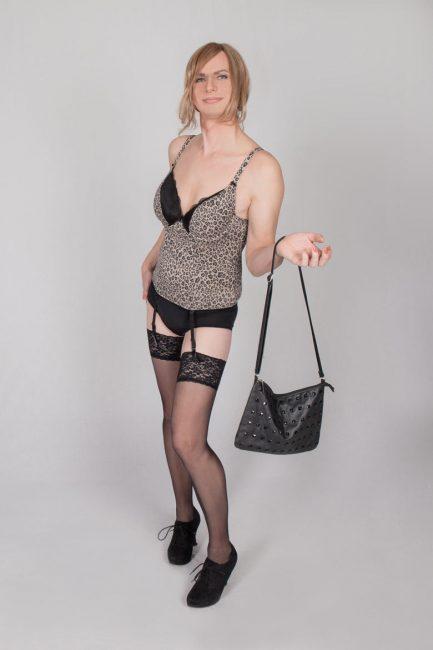Transgender Modell mit schwarzen Strapsen und einer Handtasche, sowie einem Body als Oberteil